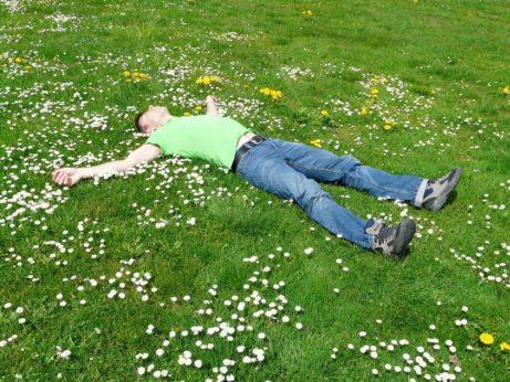 Muž leží na louce a medituje