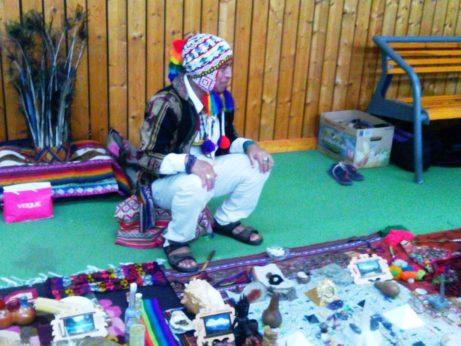 andský šaman Don Sergio před rituálem hojnosti, za ním čelenka s pavími pery